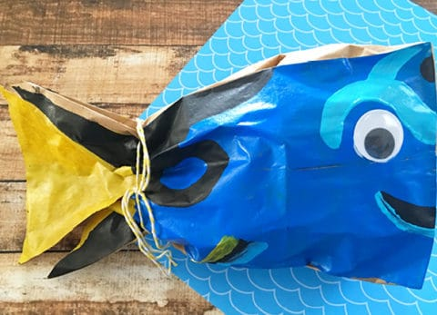 Use your black paint, light blue, and yellow paint to paint Dory's designs on the bag as shown. If you need some guidance, use your sharpie marker to draw on the bag before you start painting. Glue one plastic googly eye onto the top right of the bag. Once your bag is dry, ball up a couple lunch sacks and place them inside your painted bag. Now tie a piece of yellow twine around where the yellow and blue paint meet and you've got a cute little Dory bag.