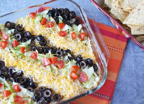 This taco dip recipe is best made the day before and will easily please a crowd!