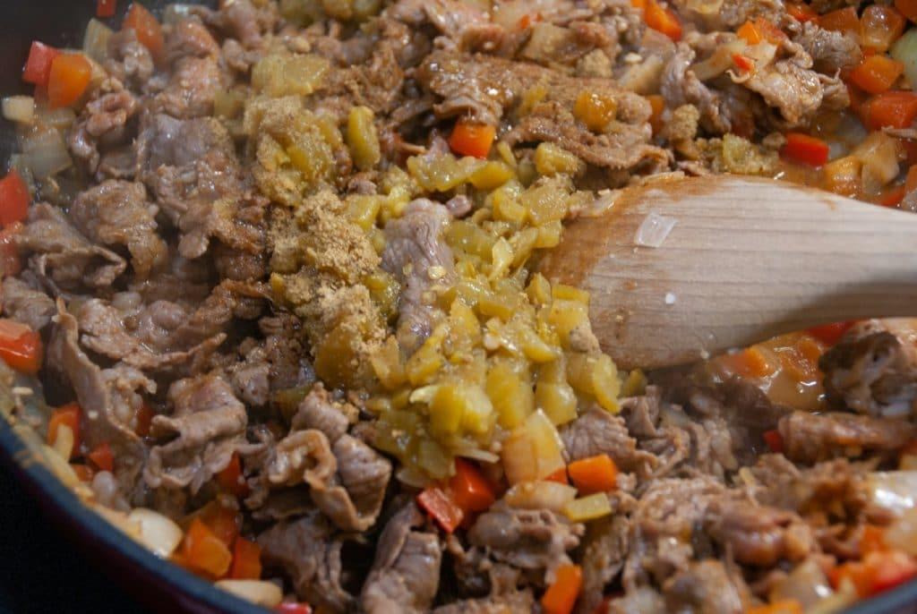 Adding green chilis to skillet