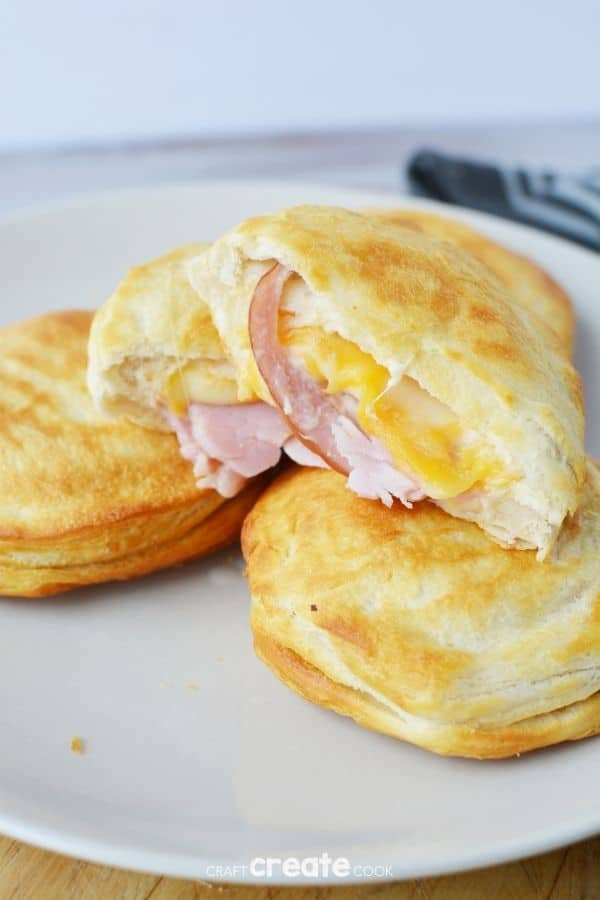 Ham and cheese biscuit sandwiches stacked on a white plate