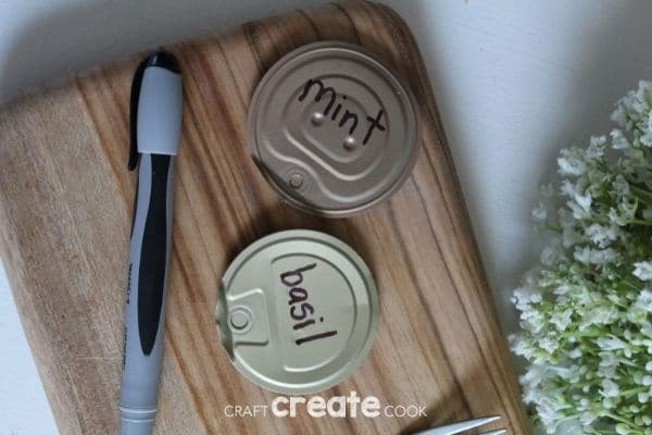 Writing plant name on tin can lids